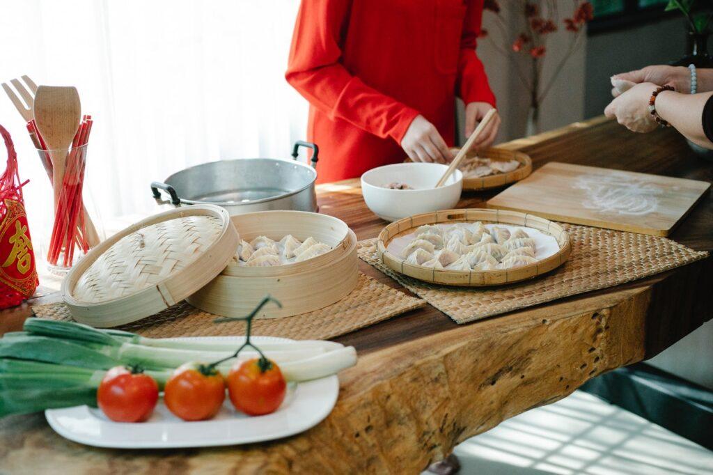 woman making dumplings in a kitchen