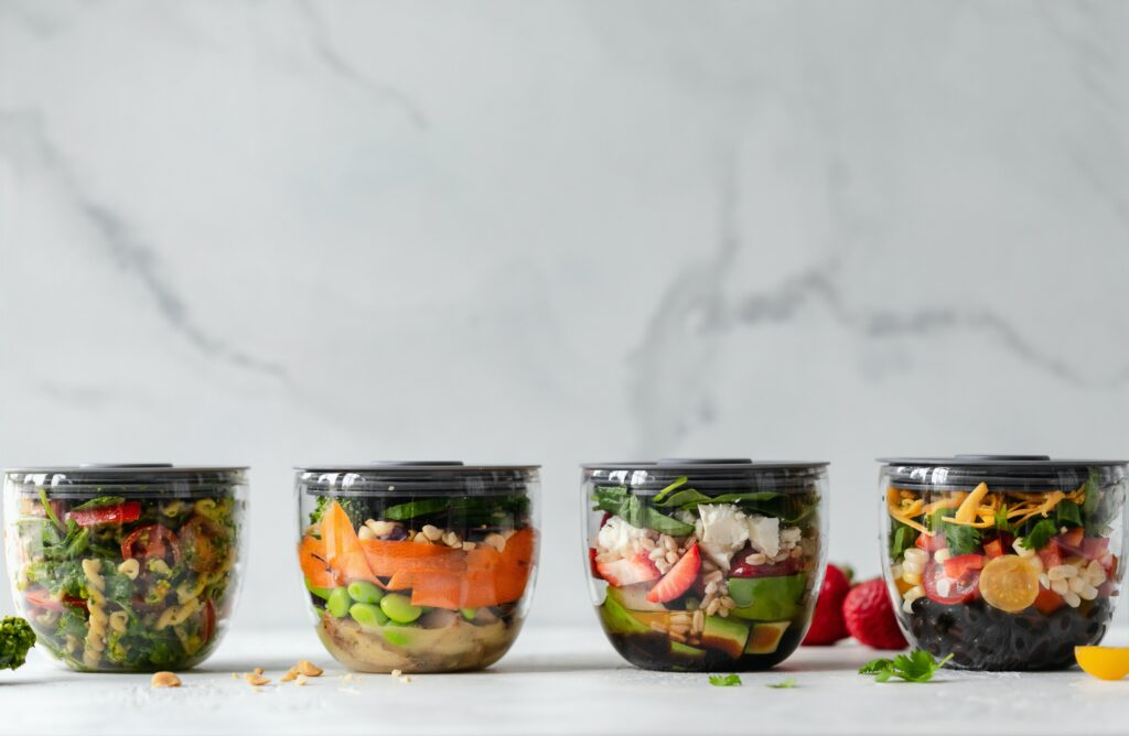 5 Salad Meal Prep recipes in glass containers on a counter top