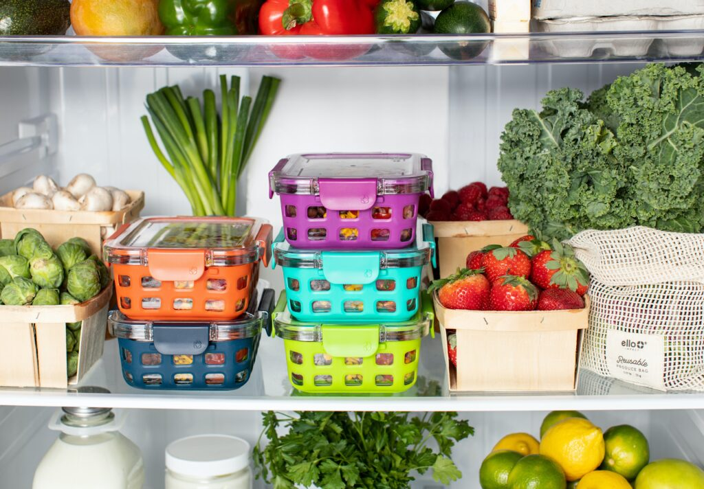5 Whole30 Meal prep containers in the fridge with strawberries and other produce